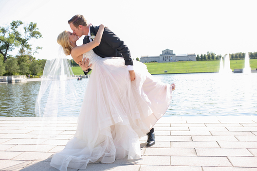 wedding couple kissing in front of fountain lake