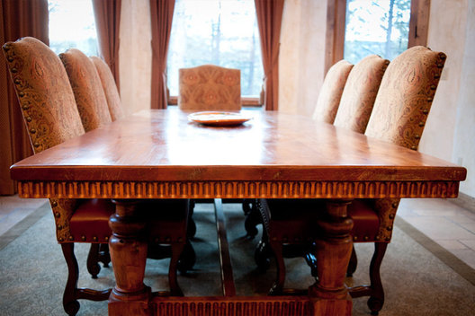 We customized this dining table with carved details and added a custom wool rug at the foot.
