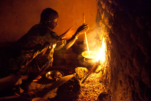 "A woman in Djibo, Burkina Faso rolls a spatula between her hands to cook millet ""pot,"" similar to the Italian polenta.  Without a stove or electricity, women throughout West Africa cook outside on an open fire."