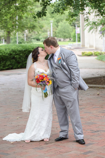 wedding couple kissing in courtyard