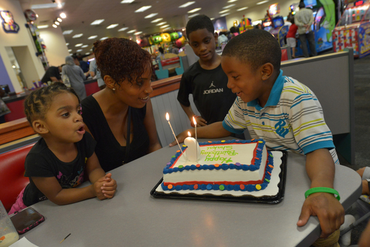 Caressa takes her family to Chuck E Cheese for her son's birthday.  They don't cut the cake there but take him home and use it for a second party with neighbors.