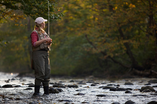Young woman fly fishes on a river in Central Vermont, 2009.  This image has a signed model release.