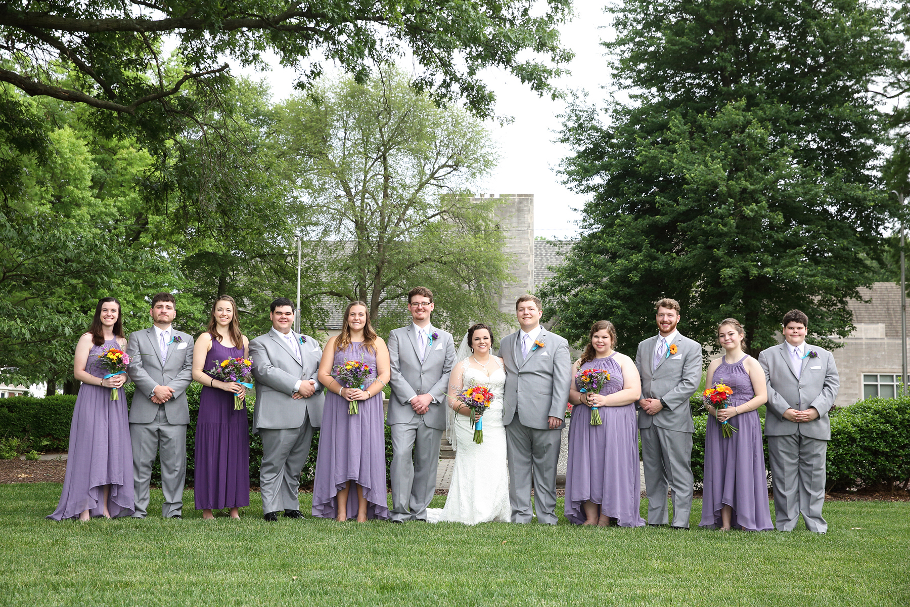 wedding party group in purple dresses and gray suits