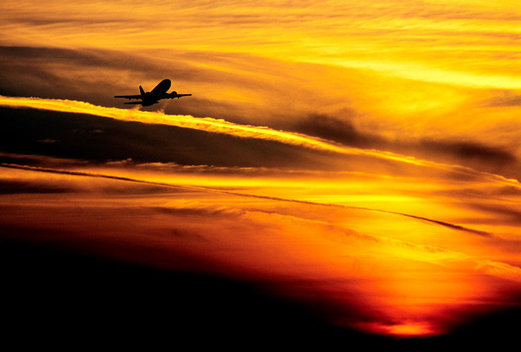 A commercial airliner flies into the sunset.