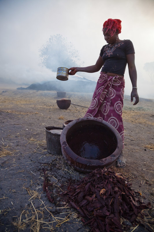 Next to the kilns, a woman separates the red bark of a certain tree from the water it has been soaked in.  The red-dyed water will be used as a decorative glaze for the pots yet to be fired.  The glaze is most often applied to the neck of the pot.