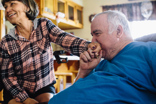 Scott Douglas, right, kisses the hand of his wife and caregiver, Sandy, at their home in Coalinga, Calif. on Wednesday, Mar. 23, 2015.