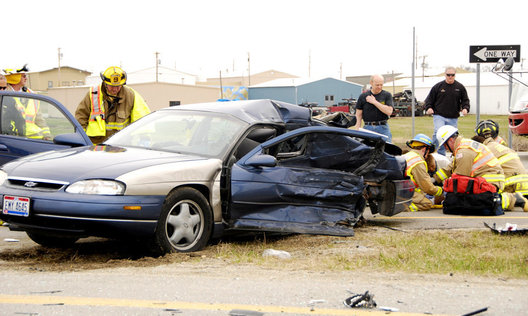 A Chevy Monte Carlo sits in the meridian of the U.S. Route 127 highway and Sebring-Warner streets intersection in Greenville after colliding with a truck on March 27 as emergency workers try and help a young toddler boy with injuries in the background. One woman, Billie Kress, 25, of Greenville, was ejected from the car and was pronounced dead on the scene. Melinda Holliday, 26, also of Greenville (a passenger in the car) died later at the hospital.