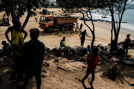 Villagers watch as the dump trucks collect sand from their beaches.