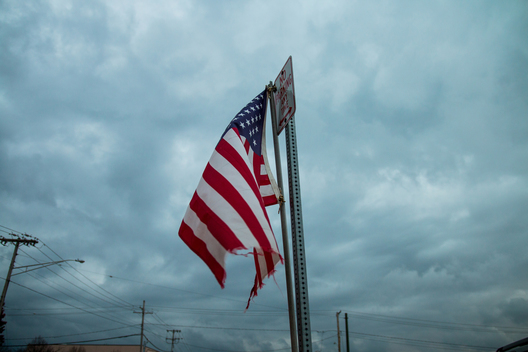Baltimore, United States/November 9, 2016 - A tattered American flag dangling from a pole in the middle of a freeway struggles to fly under a cloudy Baltimore sky the day after Donald Trump was elected president of the United States.