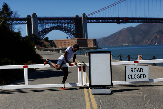 A runner climbs over a road gate leading to Fort Point National Historic Site, which has been closed due to the federal government shutdown, in San Francisco, California October 2, 2013. Cancellations and delays caused by the federal government shutdown spread across the United States on Wednesday, ruining dream vacations, upending carefully laid wedding plans and complicating the lives of millions of people.