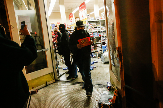 A looter leaves a Smart & Final food and supply store during a demonstration following the grand jury decision in the Ferguson, Missouri shooting of Michael Brown, in Oakland, California November 25, 2014. The grand jury decided on Monday not to indict a white police officer over the fatal August shooting of an unarmed black teenager