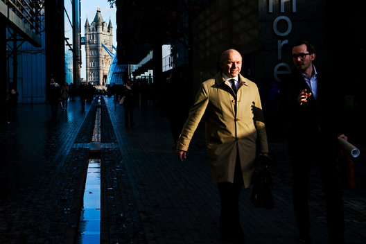 London Businessmen walking through the business district near Tower Bridge, Thames River, UK