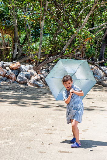 """Daddy, look at me!""  Young 6 year old girl walking along the beach carrying an umbrella, Ko Jum, Krabi, Thailand."
