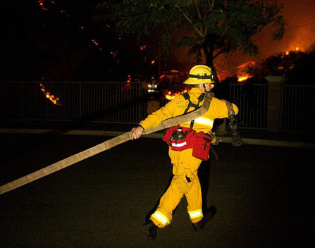 A firefighter pulls a hose to help extinguish the Brea fire on Nov. 15. Several nearby fire departments were called in to help fight the blaze, which was difficult to do because of the hills and strong winds.