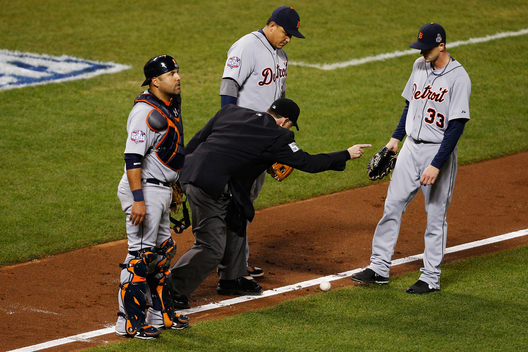Detroit Tigers third baseman Miguel Cabrera (C), starting pitcher Drew Smyly (33) and catcher Gerald Laird (L) look on as home plate umpire Dan Iassogna calls San Francisco Giants Gregor Blanco's seventh inning bunt up the third base line fair during Game 2 of the MLB World Series baseball championship in San Francisco, October 25, 2012.