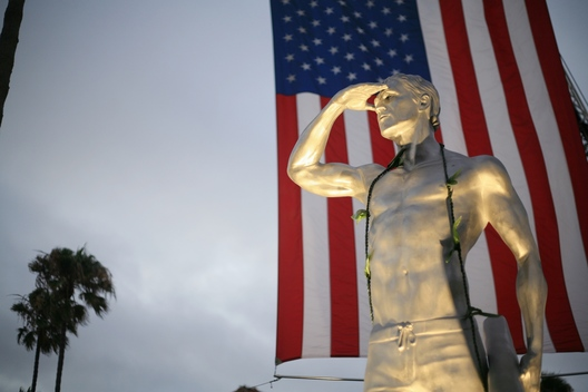 An American flag hangs behind a statue depicting Ben Carlson, the first Newport Beach lifeguard to die in the line of duty, that was unveiled Wednesday night.