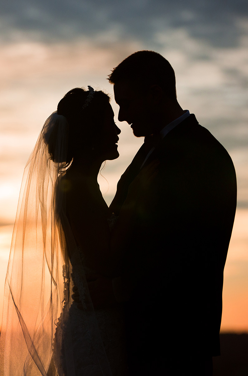bride and groom silhouette in front of the sunset at the overlook at Woodcliff for their wedding photograph in Rochester