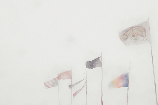 Flags flapping in a snowstorm turned blizzard at the Standing Rock camp near Cannon Ball, North Dakota