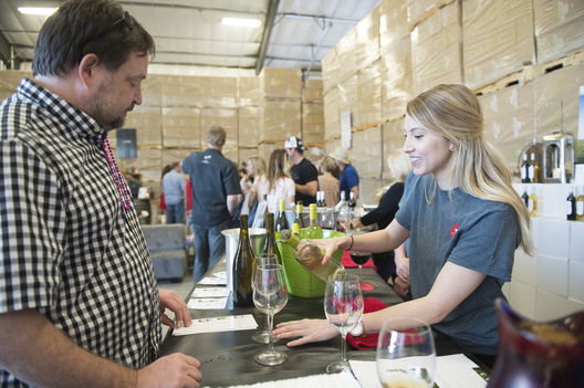 Peltier Winery's Kendall Elin (right) pours wine for Gary Kean (left) at the Lodi Wine and Chocolate festival in their new tasting room in Acampo, Ca. Dario Leventini / Lodi New Sentinel