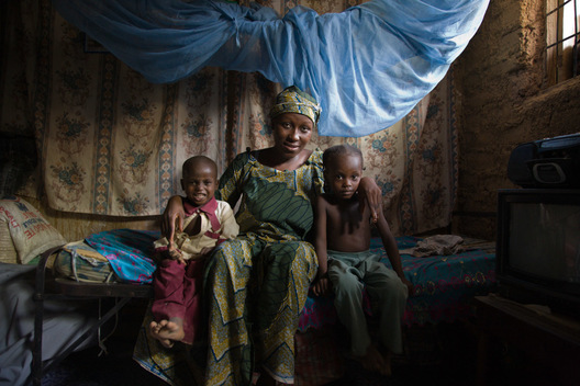 Mother and children sit under a mosquito net in Kano, Nigeria.  Distributed by Nigeria's largest indigenous NGO, the Society for Family Health, long-lasting insecticide-treated mosquito nets prevent the deadly disease, malaria.