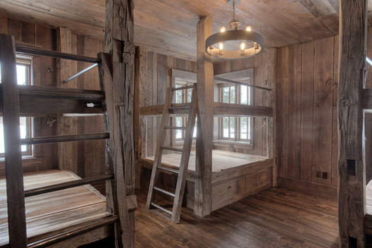 Capable of sleeping 10, the double bunks capture the corners of the rooms. Conveniently, the windows were placed so the first view of morning could take place from bed. An iron chandelier with fun edison bulbs is a focal point in the center of the room.