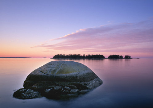 this view is from conary point on the east end of deer isle, maine.  lazygut island is on the horizon.  the boulder was just so perfectly surrounded by still water illuminated by the rising light.  deer isle has too many classic maine seascapes to count.