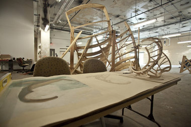 "An image of ""Structural Surfaces"" under construction and the schematic drawing and physical model on the table
