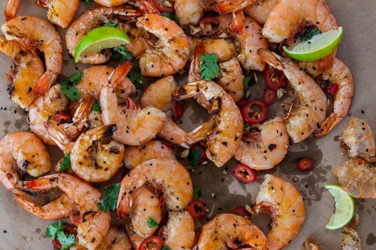 Asian-style Peel n' Eat Shrimp on brown parchment, seafood