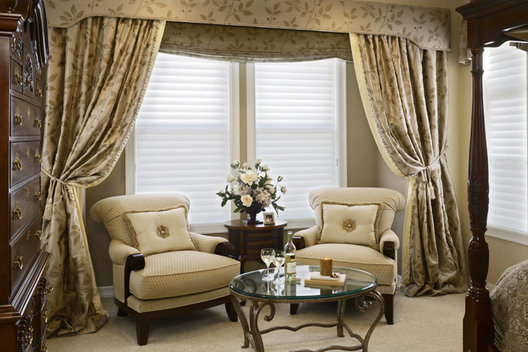 We framed this master suite bay window seating area with 25 yards of draping silvery silk, swagged back gently with french tassle tie backs. An upholstered hard cornice with braided trim crowns the top of this treatment, while a faux roman valance of the same material frames the window in the back. The diamond shimmering chenille on the chairs makes for a soft and relaxing space for reading or sipping on wine. It is both calm and very sophisticated.