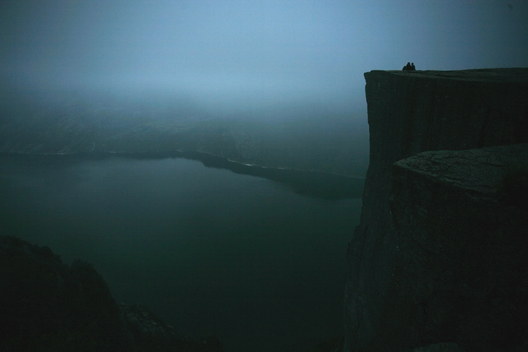 A couple sits at the top of Preikestolen (also known as Pulpit Rock), a steep cliff which rises 604 meters (1,982 feet) above the Lysefjorden near Stavanger, Norway, during a foggy sunrise around 4:30 a.m. on a summer morning.