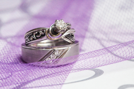 wedding rings on top of purple netting