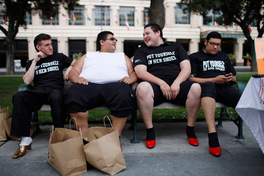 (l-r) Bill Kincaid, Antonio Ayala, Robert Barrientos, and Chuy Jimenez, of share a bench while wearing women's high-heels during the tenth annual Walk A Mile In Her Shoes to raise awareness against sexual violence in Plaza De Cesar Chavez in San Jose, California April 18, 2012. According to Department of Justice's National Crime Victimization Survey, an average of 207,754 cases, or one victim every two minutes, of rape and sexual assault were reported between 2006-2010.