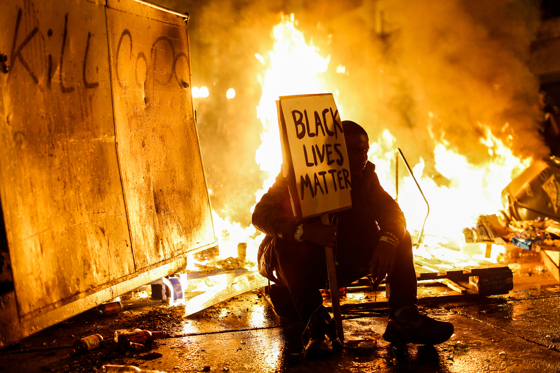 A demonstrator sits in front of a street fire during a demonstration following the grand jury decision in the Ferguson, Missouri shooting of Michael Brown, in Oakland, California November 25, 2014. The grand jury decided on Monday not to indict a white police officer over the fatal August shooting of an unarmed black teenager.