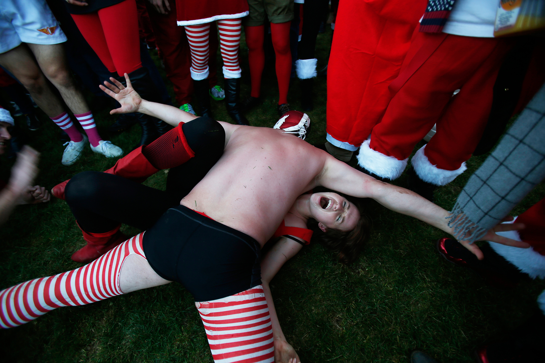 Jill Corey (below) reacts while wrestling with Dan Robertson (above) as holiday revelers dressed as Santa Claus gather in Duboce Park during the SantaCon event in San Francisco December 14, 2013.