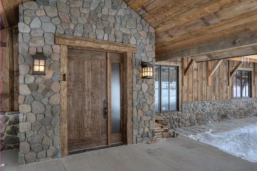 The front entry under a massive porte cochere protects in harsh mountain winters. River rock from the nearby stream adorne the walls.