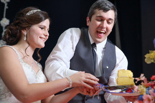 couple laughing as they cut the cake
