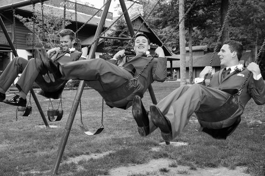 Groom on swings with groomsmen