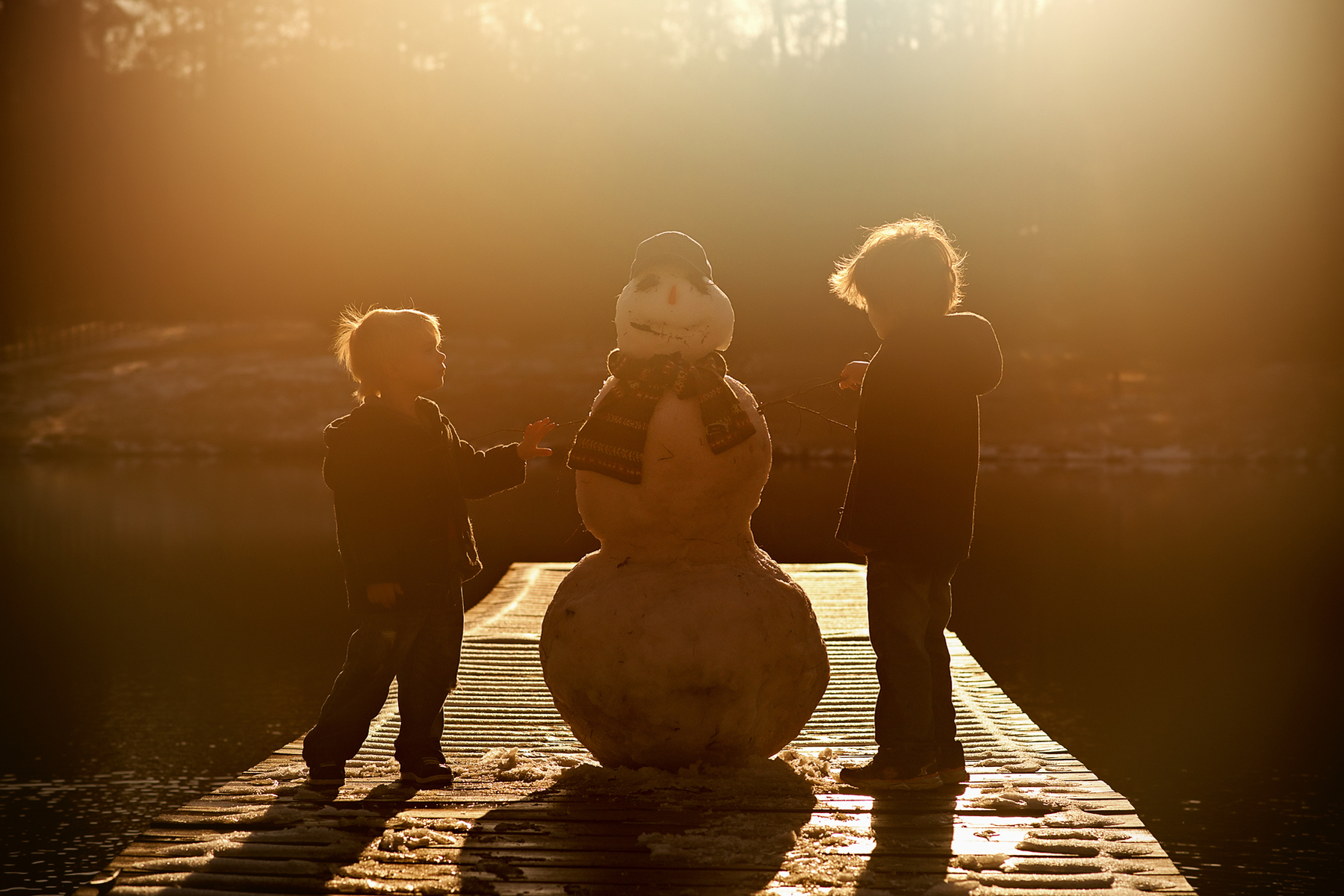 Two boys and their snowman on a dock at sunset