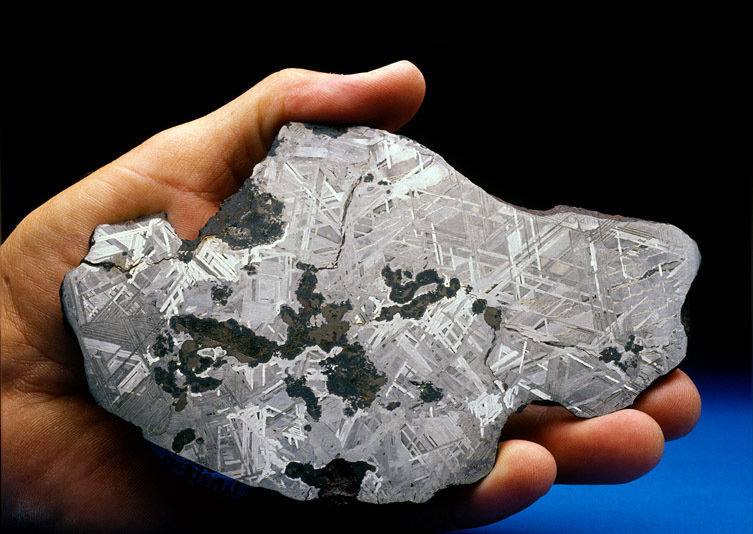 This is a new discovery southwest of the Gibeon Strewnfield.  The shape of the specimin was very unusual.  When we polished and etched a small wimdow into the meteorite, the very different Widmanstatten pattern was proof we had found a new one.  This is a graphite, troilite and silicate rich.  From Robert Haag's private collection.