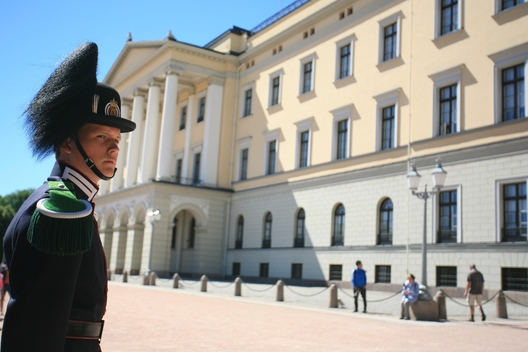 A guard watches over Oslo Royal Palace as tourists look on from the sidelines.