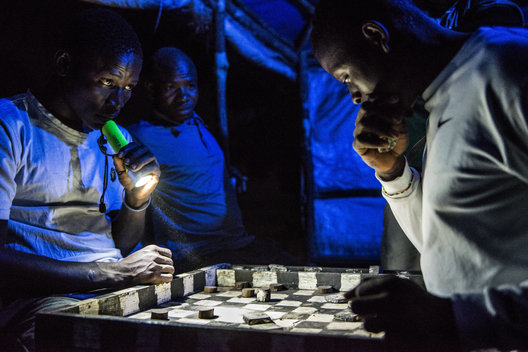 Village fishermen unwind with a game of checkers before heading out for a night of fishing. The fishermen's catches have continued to dwindle due to illegal fishing by commercial industrial trawlers. As a result, the fisherman paddle their boats further out into the ocean.