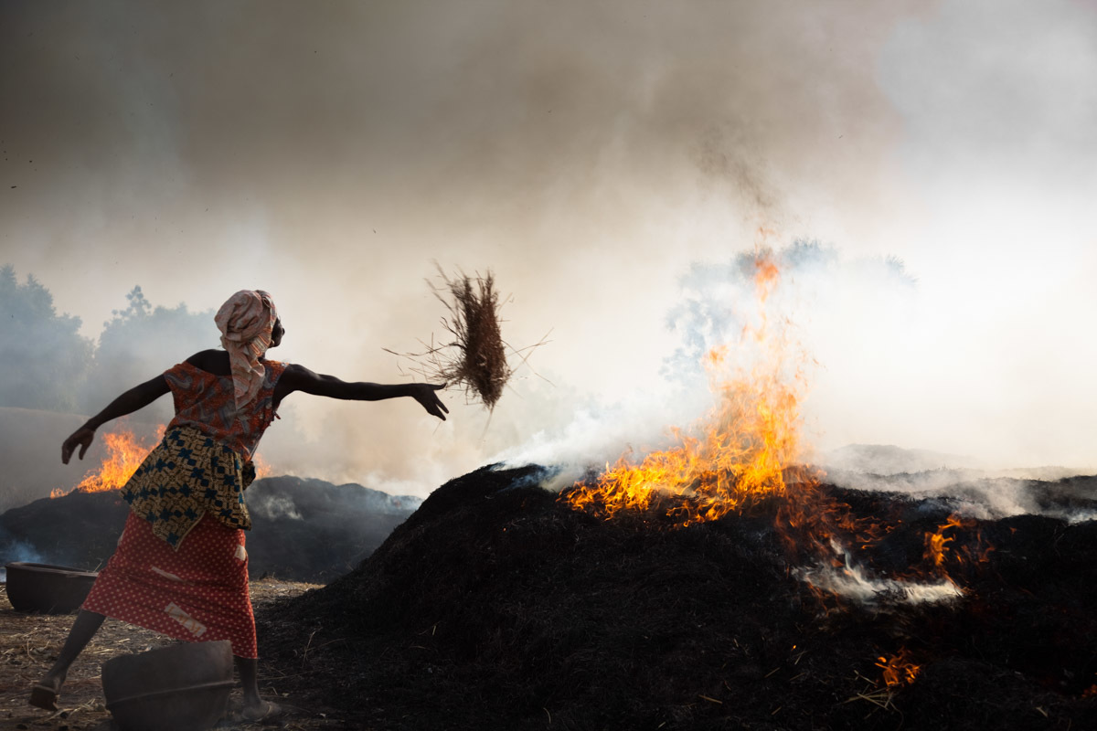 A woman in the village of Kalabougou in Mali throws fire on a giant stack of hay, under which are buried pots to be fired in this kiln.