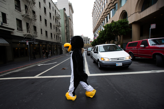 Ali Mazzotta, center, of CLASH Scavenger Hunts, walks towards Union Square while wearing a penguin suit for teams of scavenger hunters in San Francisco, Calif. on Thursday, Oct. 11, 2012.