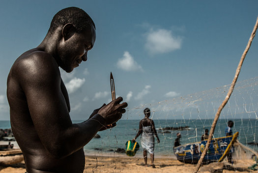 A fisherman makes repairs to his net.  Quite often the local fishermen's nets are damaged by the pirate boats.