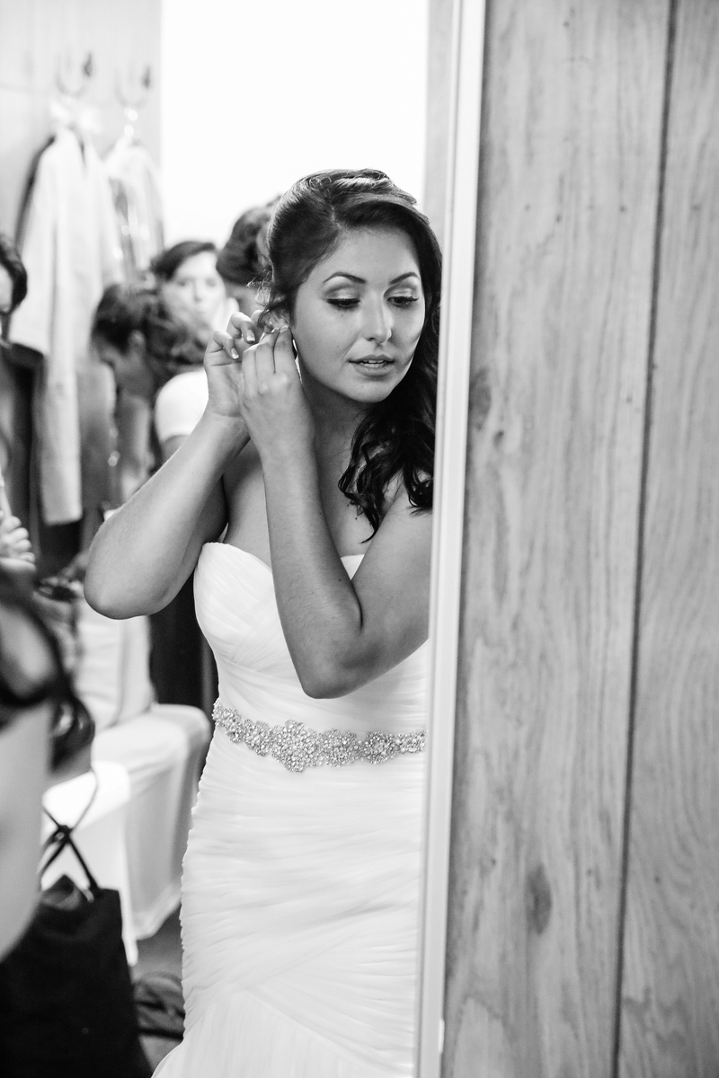 bride adjusting jewelry in mirror