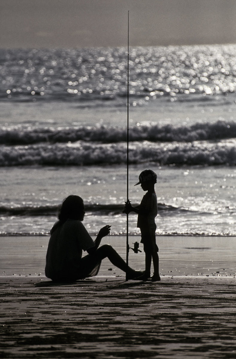 Father teaching his son to fish.  It's a day and lesson the boy will probably remember and treasure forever.