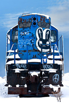 An image of a retired locomotive covered in rust, graffiti, and snow in Minnesota