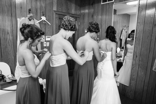 4 women in a line adjusting dresses