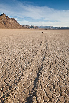A boulder trail is carved into the dry lakebed, stretching for a quarter mile. The Racetrack, Death Valley National Park, Calif.