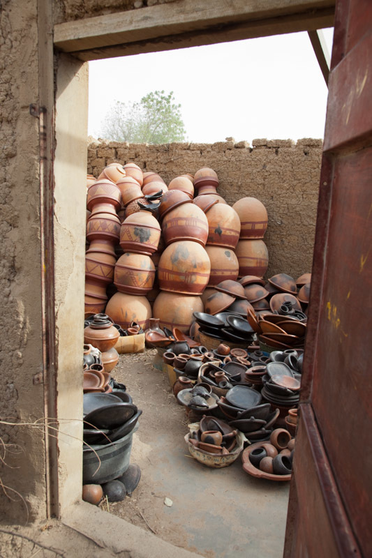 Completed pottery is stacked in an open warehouse, ready for transport to market.